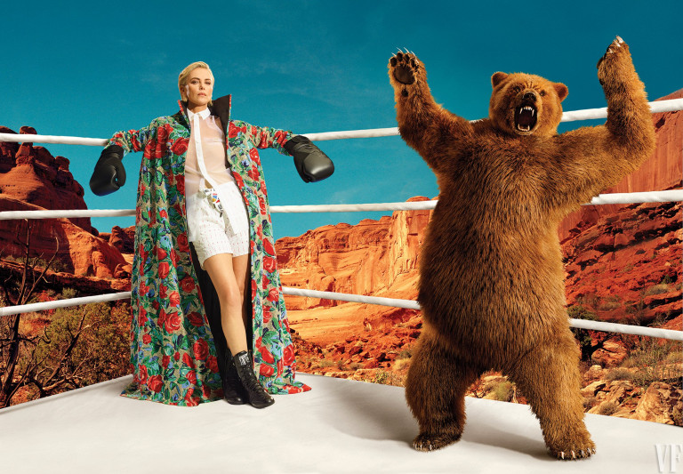 Charlize Theron poses in a boxing ring with a bear