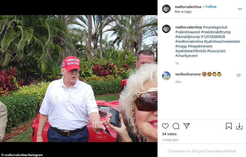 Trump is pictured preparing to take a photo with guests at Mar-a-Lago attending a car show fundraiser for a local charity
