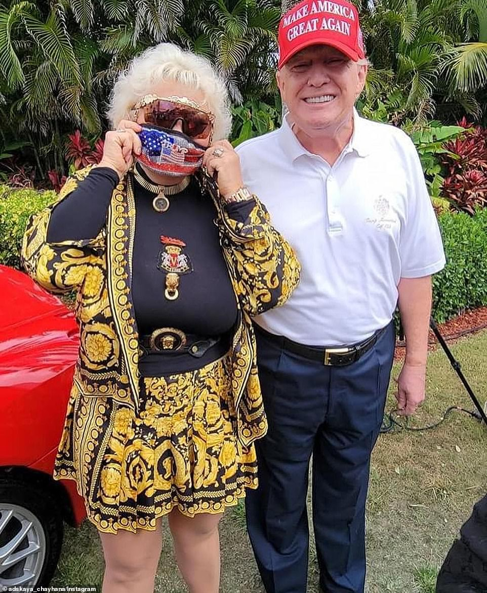 A woman puts on her mask to take a photo with former President Donald Trump, right, as he greeted guests at his Mar-a-Lago resort on Sunday