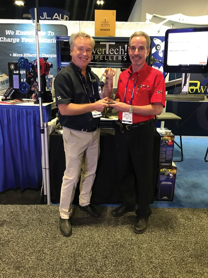 Steve Powers (black shirt) and Marcus Clements with one of the company's many innovation awards.