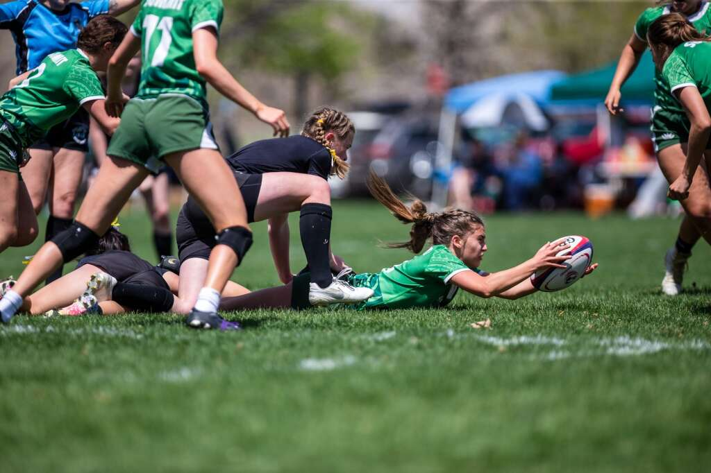Bryton Ferrari dives to save the ball as a Monarch player tackles her during the first of three games played at the high school rugby state championship on Saturday, May 1, 2021, at Cook Park in Denver. The Summit High girls rugby team won their 13th-straight state championship title. | Photo by Liz Copan / Studio Copan