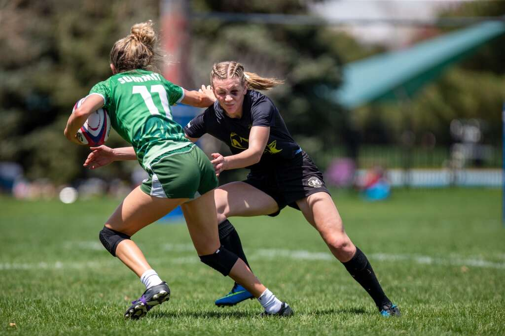 Olyvia Snyder stiff arms a Monarch player during Summit High School' state championship victory over Monarch on Saturday, May 1 at Cook Park in Denver. | Photo by Liz Copan / Studio Copan