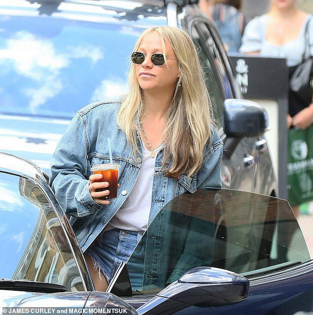 Style:She opted for a double denim look with the jacket and completed her stylish summer ensemble with white trainers and a black leather back pack