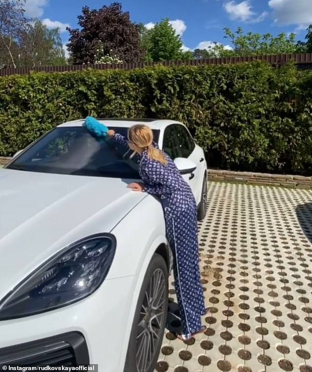Yana Rudkovskay urged her five million subscribers to vote but was hit by a barrage of criticism. Pictured, dusting one of her four Porsches