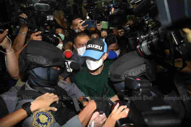 Pol Col Thitisan Utthanaphon is taken from the Crime Suppression Division to the Muang police station in Nakhon Sawan on Thursday night. (Photo: Arnun chonmahatrakool)