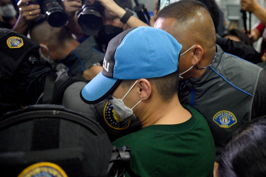 A man in a face mask and baseball cap surrounded by police and camera operators gets into a car
