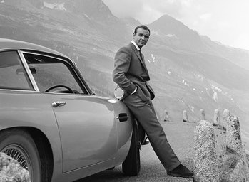1964:  Actor Sean Connery poses as James Bond next to his Aston Martin DB5 in a scene from the Unite...